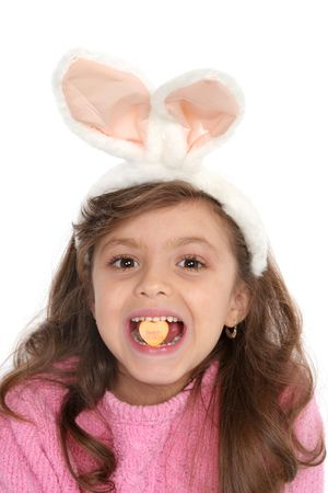 Cute girl with bunny ears holds a candy in between her teeth that reads sweet hearts