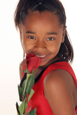 young African American girl smells her red rose