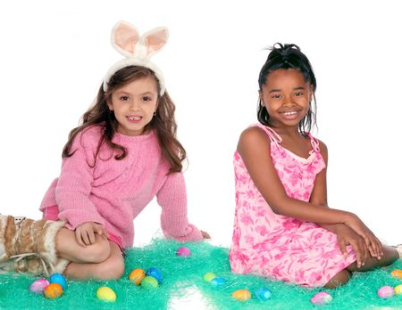 Two girls sitting with Easter eggs on green holiday grass