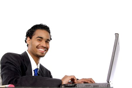 diligent young man smiling as he works on his computer