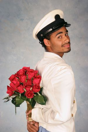 attendant waiting with bouquet of red roses in white jacket and hat