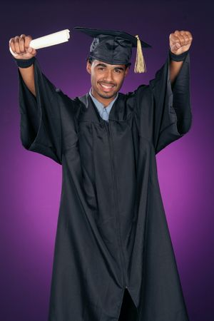 young man with his arms raised is celebrating his achievement as he graduates
