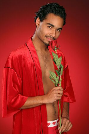 gallant guy in red stops to smell the rose Imagens