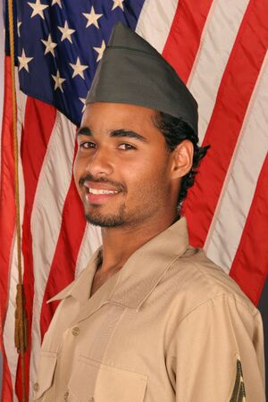 duty: duty bound young man smiles nervously in front of American flag Stock Photo