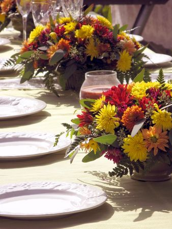 outdoor table setting with flowers in fall colors red yellow golds and orange with white plates cystal glasses in the background