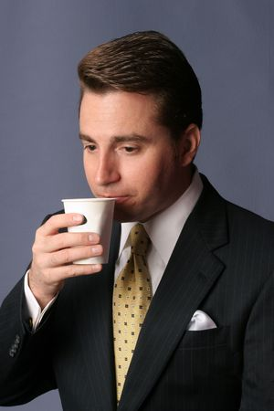 businessman sips cup of coffee on blue background