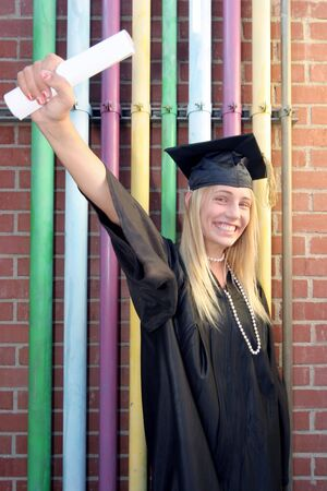 Young Girl in her cap and gown graduates smiling she holds up her diploma in front of colorful background Stock Photo