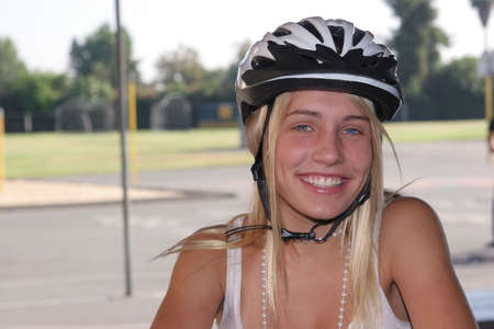 Beautiful young girl wears her bike helmet for cycling as a casual sport