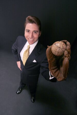 businessman holds the world in his glove on black backdrop Stock Photo