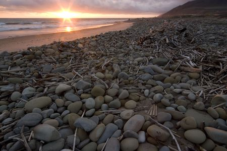 Driftwood and stones left on beach after a storm at sunset in Ventura, Ca.