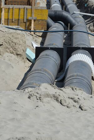 metal pipes with insulation underneath the road on the construction site