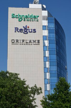 BELGRADE, SERBIA - JUN 9, 2019: Schneider Electric, Regus and Oriflame logos together in their office building in Belgrade, Serbia