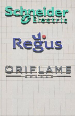 BELGRADE, SERBIA - JUN 9, 2019: Schneider Electric, Regus and Oriflame logos together on the business building in Belgrade, Serbia Éditoriale