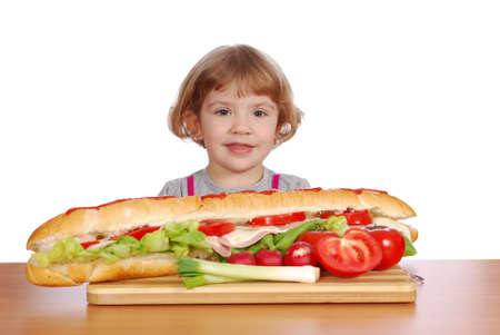 little girl with big sandwich on table photo