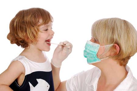 doctor examines throat in little girl patient photo
