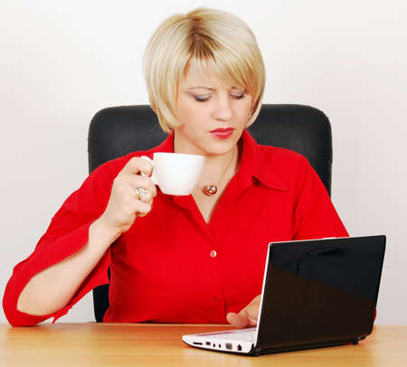 woman with coffee-cup and laptop photo