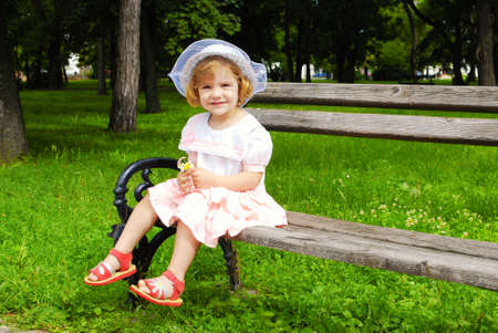 little girl sitting on the bench in park photo
