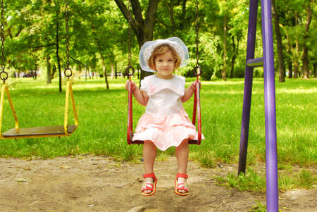 little girl sitting on the swing photo