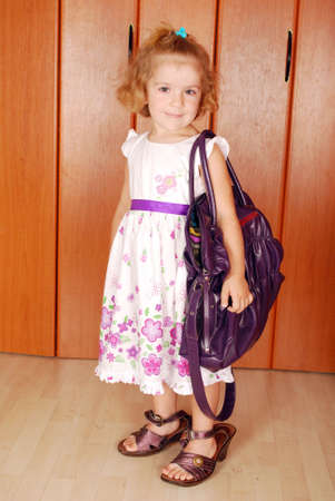 little girl with big bag and shoes  photo