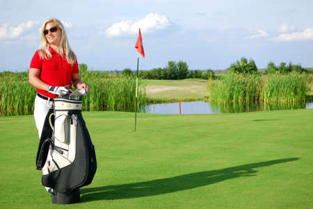 girl with golf bag on golf course photo