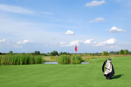 golf field with red flag and bag photo