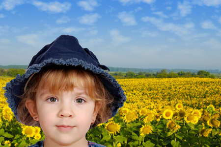 little girl portrait with sunflower field behind photo