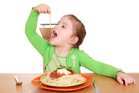 four years hungry little girl eating spaghetti