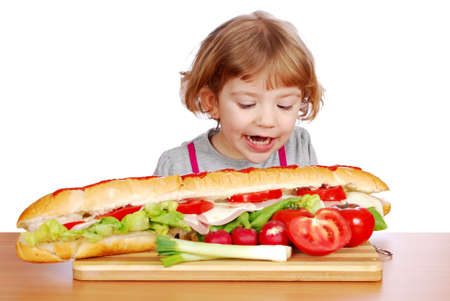 hungry little girl tries to eat big sandwich  photo