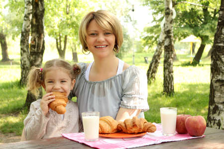 mother and daughter breakfast in nature