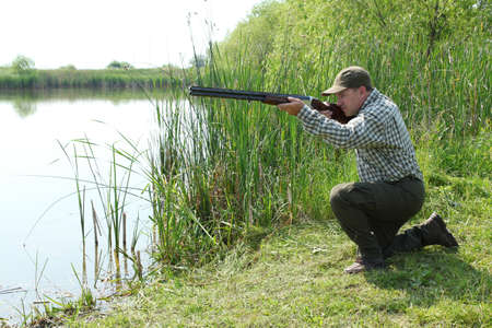 hunter aiming and ready for shot wild duck hunting photo