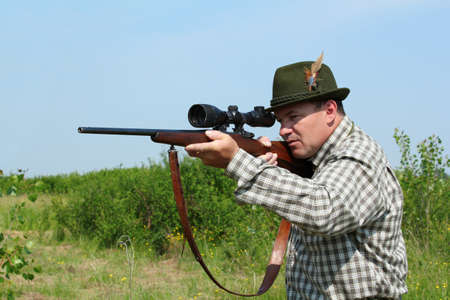 hunter aiming with sniper rifle photo