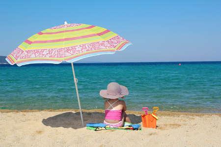little girl sitting on beach under sunshade