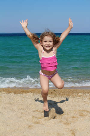 happy little girl jumping on the beach photo