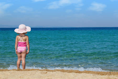 little girl looking at sea photo