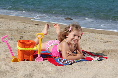 little girl lying on the beach Stock Photo - 10094952