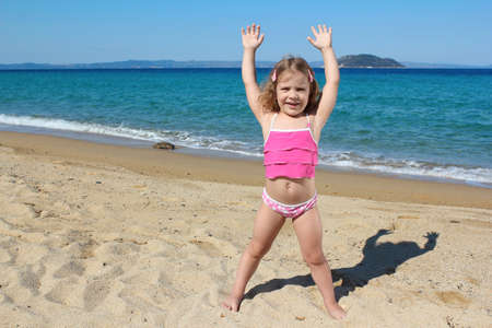 little girl with hands up standing on the beach Stock Photo