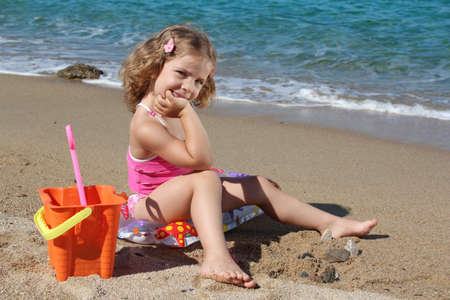 little girl with toys posing on the beach photo