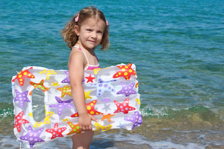 little girl with airbed standing in the sea photo