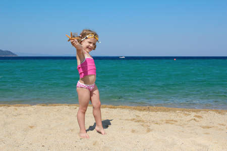 little girl with starfish and goggles on beach photo