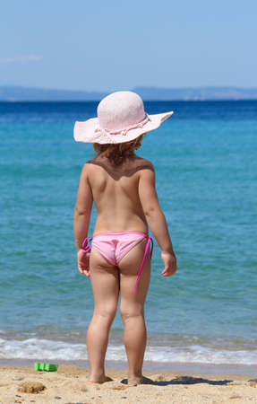 backside: little girl with straw hat looking at sea Stock Photo