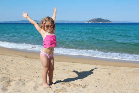 happy young girl with hands up on the beach Stock Photo