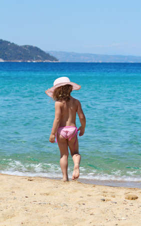 little girl with straw hat walking on beach Stock Photo
