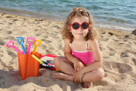 little girl with sunglasses sitting on beach photo