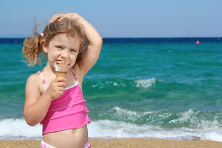 young girl with ice cream on the beach photo