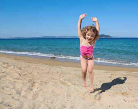 happy little girl jumping on the beach Stock Photo