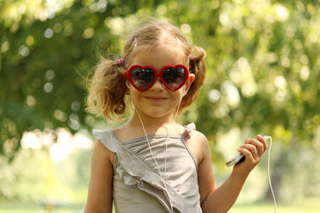 little girl with sunglasses listening music photo
