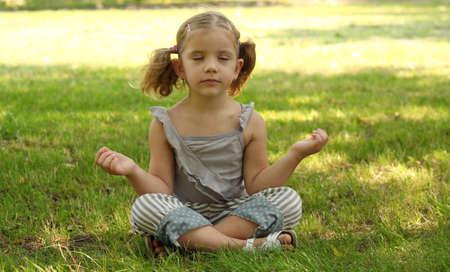 little girl meditating in park photo
