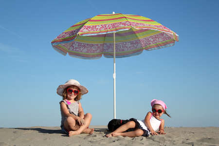 two little girl under sunshade photo