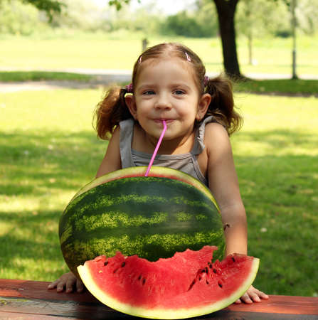 red straw: beauty little girl with watermelon summer scene Stock Photo