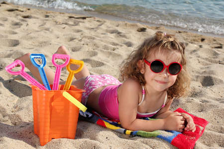 little girl with sunglasses on the beach photo